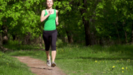 Stock Video Footage of Runner feet running on a rural road closeup. Woman fitness concept. Slow motion.