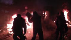 Stock Video Footage of Protesters throw automobile tires in the fire.