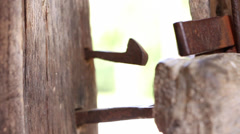Female hand closes old wooden door with an iron latch - stock footage
