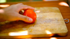 Female hands sliced tomato on a wooden board. Macro video Stock Footage