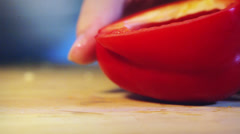 Cutting red pepper on wooden board - stock footage