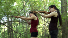 Wide view of two women firing rifles in woods HD Stock Footage