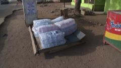 Car Drives Past Pallet of Sachet Water in Accra, Ghana Stock Footage