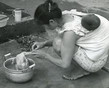 Stock Photo of Vietnamese refugee mother prepares meal , Hong Kong 1980s