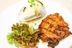 Pork steak with baked potato Stock Photos