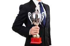 Businessman awarded with prize cup isolated on white - stock photo