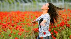Happy teen enjoys emotions in poppy field Stock Footage