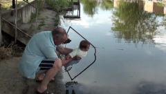 Granddad amuses baby near river - stock footage