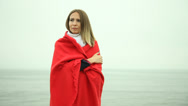 Stock Video Footage of Lonely sad girl in red blanket on the sea shore