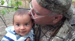 Man in camouflage kissing baby Stock Footage