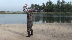 Man in camouflage throws a baby up and catches Stock Footage