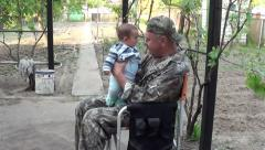 Man in camouflage plays with baby Stock Footage
