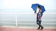 Stock Video Footage of Woman with umbrella relaxing on the pier. Sea.