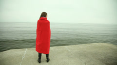 Lonely girl in red blanket looking at the sea Stock Footage