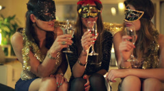 Girlfriends in masks raising toast during masquerade party HD Stock Footage