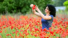 Happy woman in poppy flowers field at spring time Stock Footage