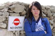 Stock Photo of Pouty girl standing by NO ENTRY sign