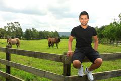 man sitting on th efence of a horse paddock - stock photo