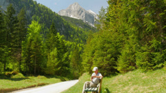 Man sit on the bench in the mountains and holds Smartphone in the hand. Stock Footage