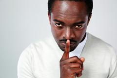 portrait of african man with finger on lips over gray background - stock photo