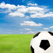 soccer ball with green grass field against blue sky - stock photo
