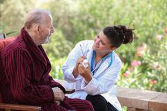 dr or nurse giving medication to senior patient. - stock photo