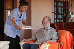 Nurse or helper in residential home giving food to senior man Stock Photos