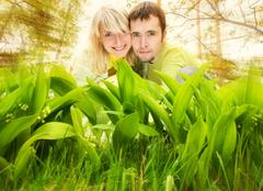 Stock Illustration of young couple hiding in fresh green grass