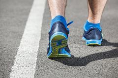Runner feet running on stadium closeup on shoe. Stock Photos