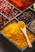 Spices in box: pink and black pepper, paprika powder, curry, bay Stock Photos