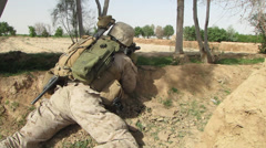 US Marine lies behind dirt berm and waits for enemy combatant  (HD) Stock Footage
