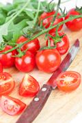 Fresh tomatoes, rucola and old knife Stock Photos
