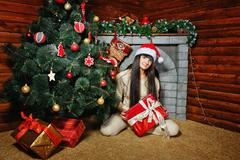 Girl with gifts near Christmas tree - stock photo
