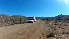 Toyota RV On Gravel Road In Desert Comes Toward And Past Camera Stock Footage