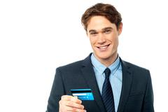 Cheerful businessman holding credit card - stock photo