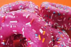 donuts coated with a pink frosting and sprinkles of different colors - stock photo