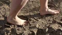 Man walking barefoot on the cracked dry ground Stock Footage