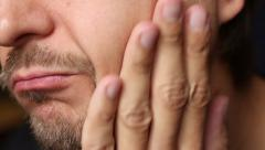 unshaven man runs a hand through his cheek - stock footage