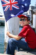 Boy on harbourside pier waving flag Stock Photos