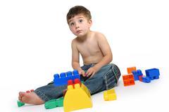 Young boy amongst building blocks Stock Photos