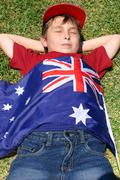 Patriotic boy with Australian flag draped over him - stock photo
