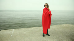 Lonely sad girl in red blanket on the sea shore Stock Footage
