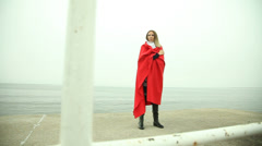 Lonely sad girl in red blanket on the sea shore HD with motorized slider. 1080p. Stock Footage