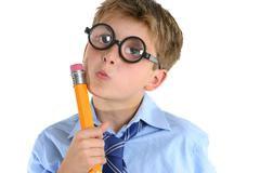 Comical boy holding a pencil and thinking Stock Photos