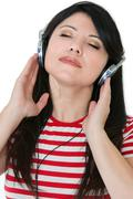 Attractive female kistens to music - stock photo