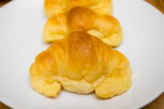 croissants on a white plate - stock photo