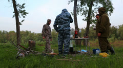 Russian fishermen drink vodka around campfire at night Stock Footage