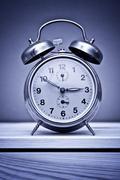 Retro alarm clock on wooden table Stock Photos