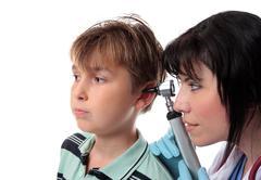 Paediatrician checking ears - stock photo