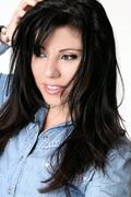 Pretty brunette girl playing with hair - stock photo